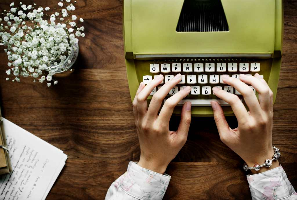 White feminine hands typing on a typewriter on a wooden desk with baby's breath in a vase nearby and written pages