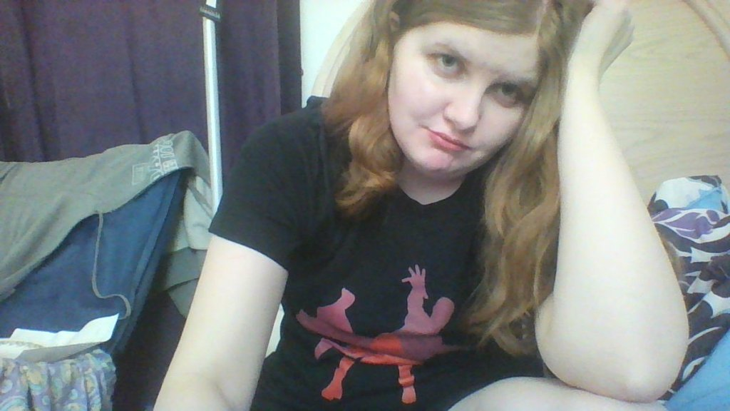 A picture of me sitting in my room in a ScarletVision shirt looking miserable